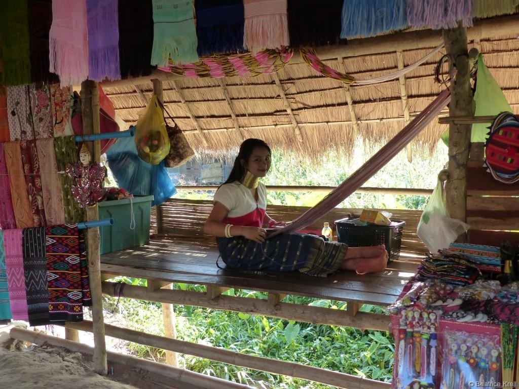 Eine Langhalsfrau beim Weben der Tücher für den Souvenirshop
