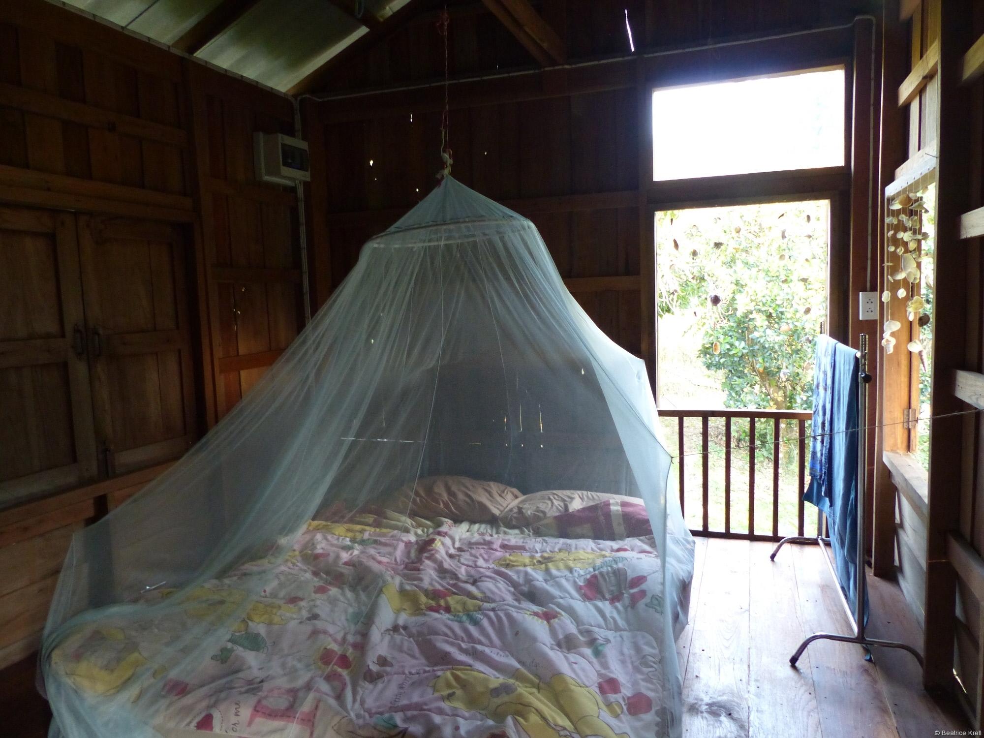 Schlafzimmer mit Bett und Muschelvorhang