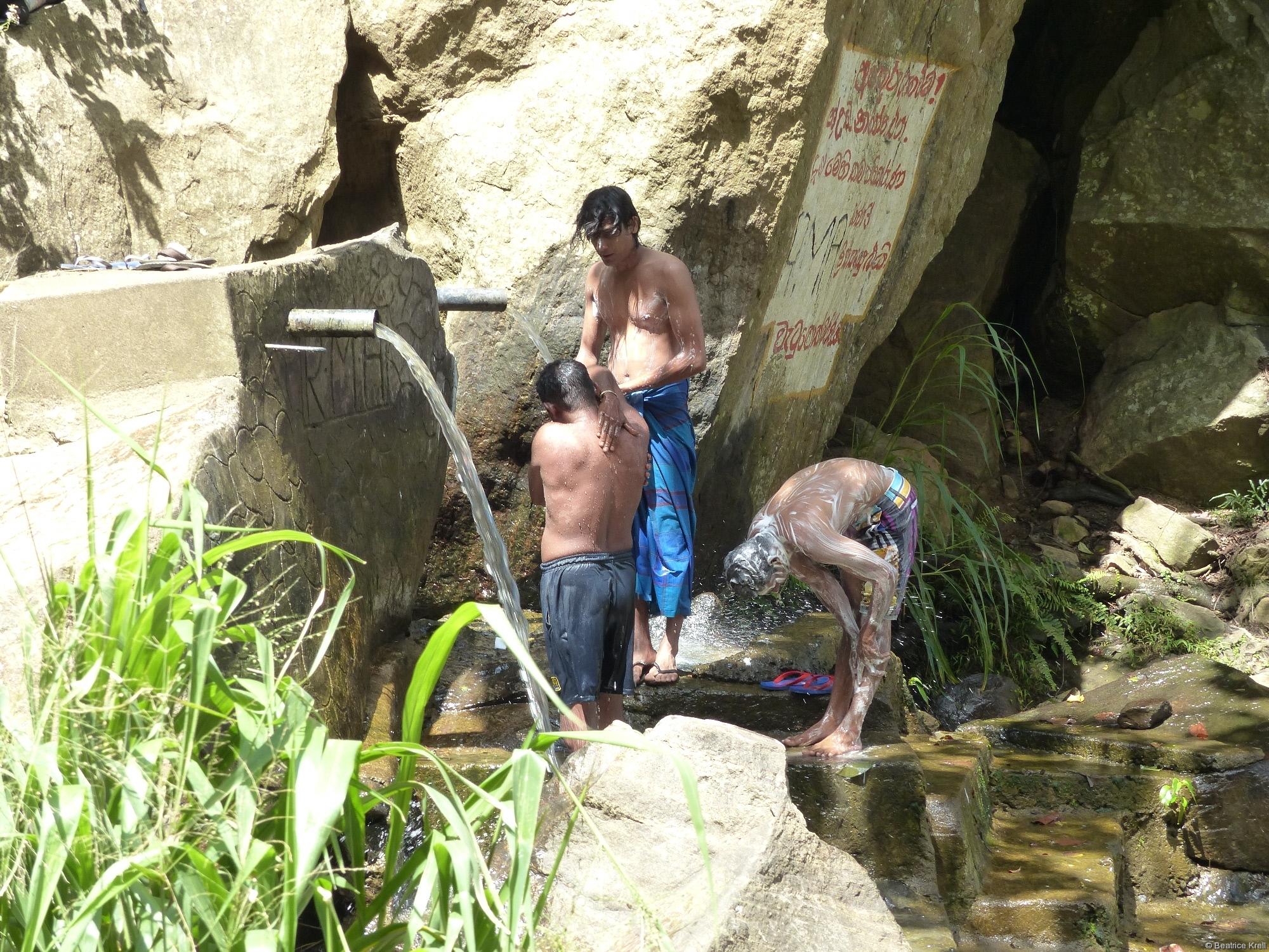 Einheimische beim Duschen am Wasserfall
